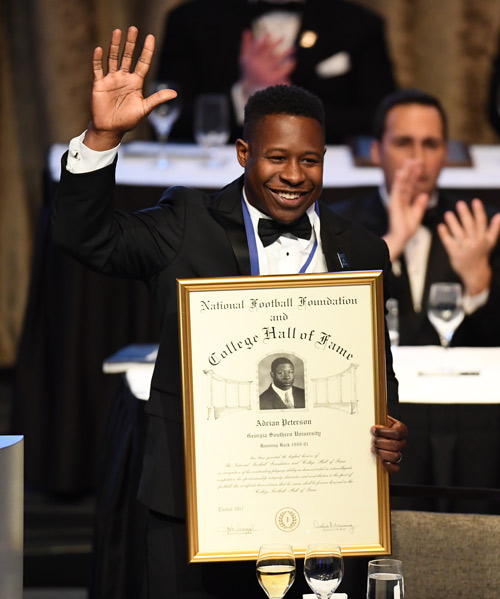 Former Georgia Southern star Adrian Peterson holding the certificate of the college hall of fame and waving