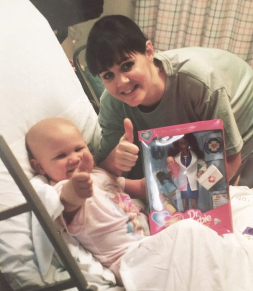 Amelia as a child in a hospital bed with no hair