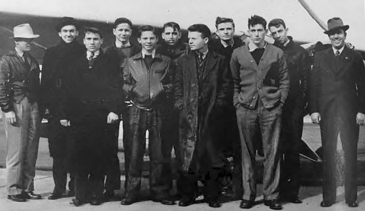 a shot from 1940 of 11 men standing in front of a small plane