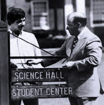 photo from 1965, two men standing around a street sign that reads: Science Hall, Student Center