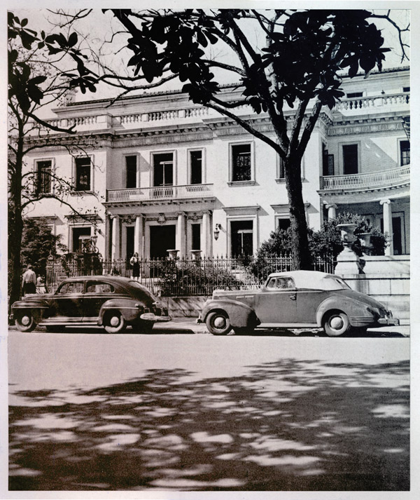 old photo showing vintage cars parking outside of the Armstrong House in Savannah, GA