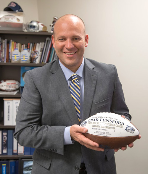 chad lunsford holding a football emblazoned with his name and the georgia southern logo