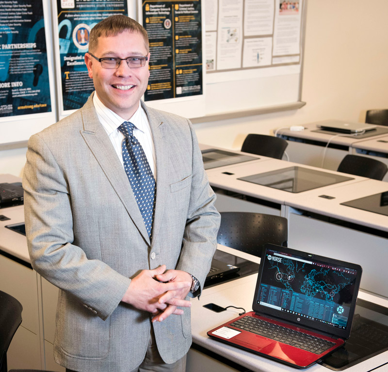 CACE Director Scott C. Scheidt standing next to a laptop in a classroom setting