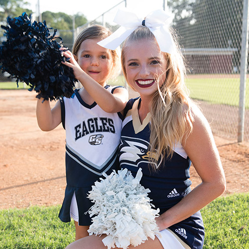 cheerleader posing with young girl holding pom poms