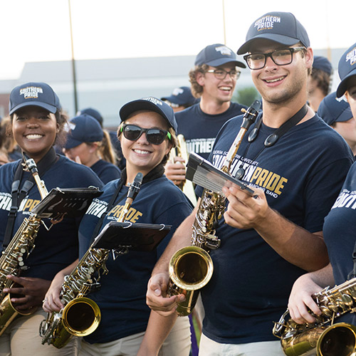 three saxophone players in the marching band