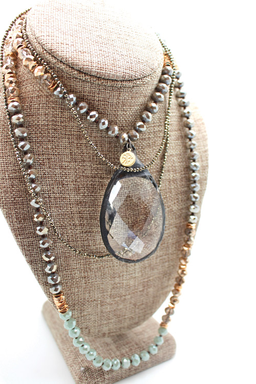 a four layer gold and silver necklace with a large clear crystal in the middle