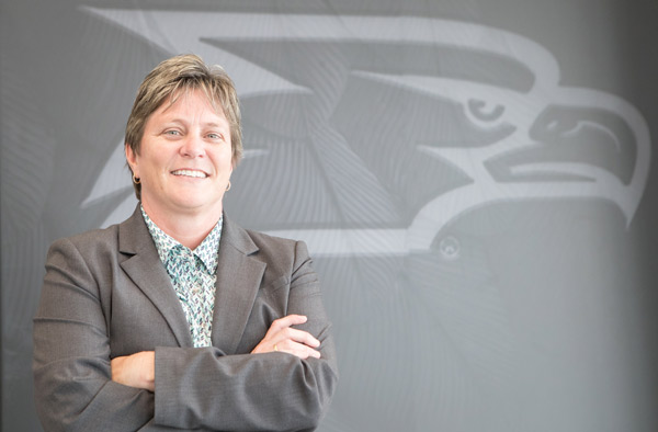 lisa sweaney standing cross armed in front of a grey Georgia Southern athletics logo