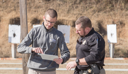 a man with an ipad explaining the technology to an officer