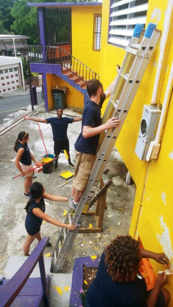 trio students painting the external wal of a building