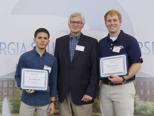 three men standing in front of a Georgia Southern backdrop two with scholarship certificates