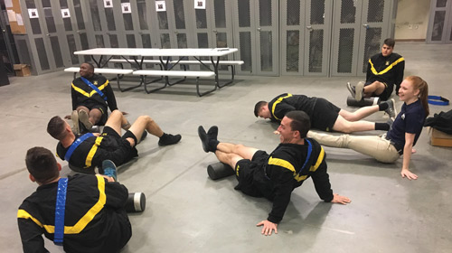 seven soldiers working out and stretching in a locker room