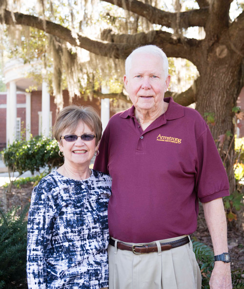 spence and sheila hoynes standing in front of a tree covered with spanish moss in front of Burnett Hall on Armstrong Campus
