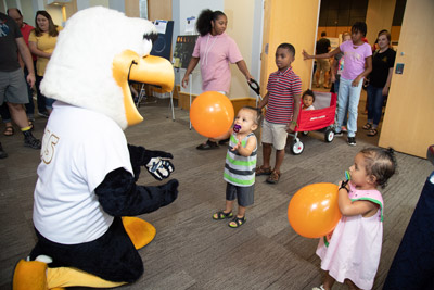 the school mascot, GUS, playing with kids