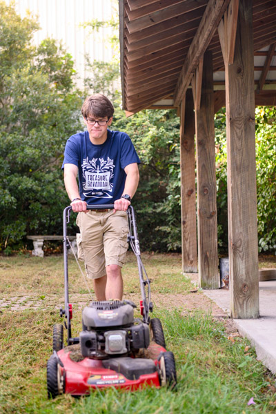 student mowing a lawn