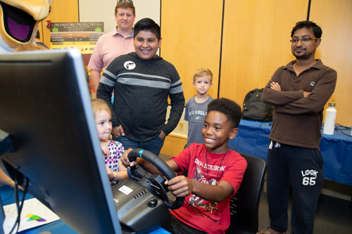 boy playing a driving game on a computer while a group of people watch on