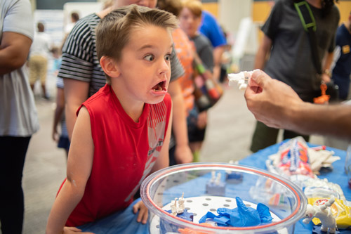 boy looking surprised while viewing a toy figure
