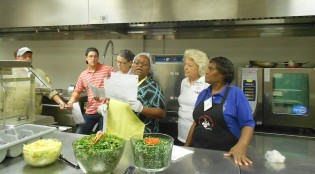 "Reba Ellis of Atlanta, Georgia reads instructions as her team readies to prepare kale slaw, vegetarian ""southern-style"" collared greens and sesame carrot salads. School nutrition managers from across the state of Georgia gathered at Georgia Southern University to attend Culinary Institute II, a 32-hour, weeklong training session by the Georgia Department of Education's School Nutrition Program. The training session includes instruction and hands-on experiences."