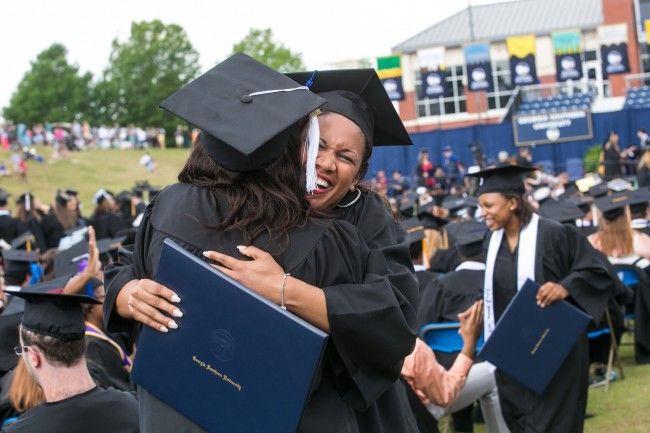 Two students embrace after receiving their degrees at the 2014 Georgia Southern University Spring Commencement ceremony.