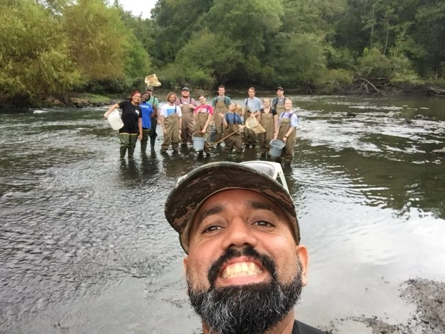 Biology professor Checo Colón-Gaud, Ph.D., stands and poses with his students in a river.