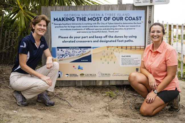 Shannon Matzke, right, poses for a picture with her advisor and Georgia Southern biology professor Lissa Leege, Ph.D., at a sign detailing her sand dune restoration project on Tybee Island.