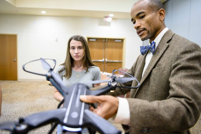 Wayne Johnson, Ph.D., examines a drone with mechanical engineering student Lydia Poole. Drones like this one will be used during the 2020 Engineering Design Challenge.