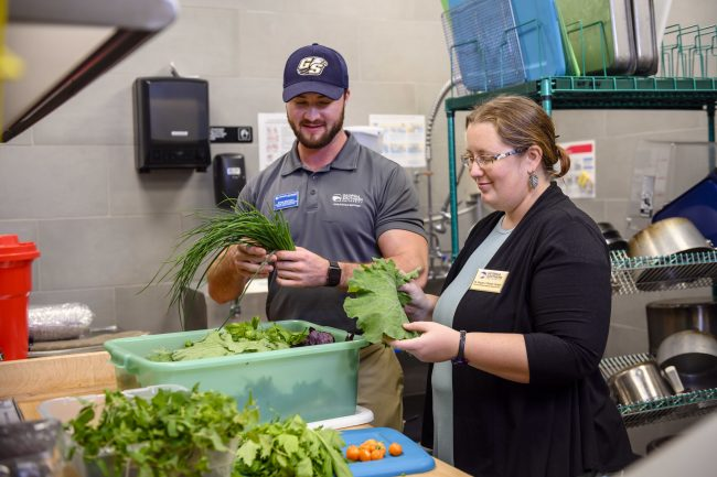 Ryan Brzycki, Assistant Director of Eagle Dining services and SARC curator Brigette Brinton sort through produce to be used at the Southern Cafe on the Georgia Southern University Armstrong Campus.