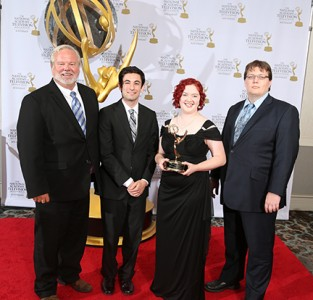Golden Emmy statue rises high in the background with 4 people, 3 men and one woman, all dressed in black as Rebecca Lynch holds a smaller Emmy in her hands.