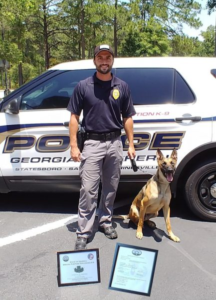 Georgia Southern Office of Public Safety officers BJ McKellar and K-9 Rocky pose with their certificates after completing trainings related to the new equipment they were recently donated.